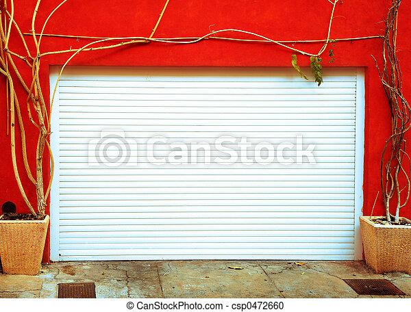 Bright orange wall with a white garage door - csp0472660