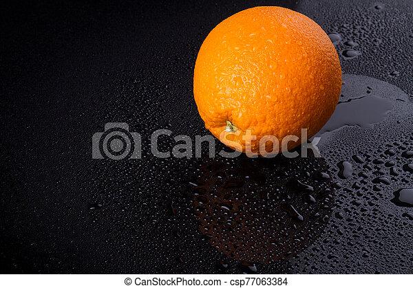 Bright orange with drops on peel. - csp77063384