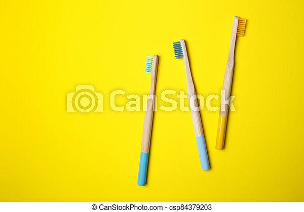 bright toothbrushes on a yellow background - csp84379203