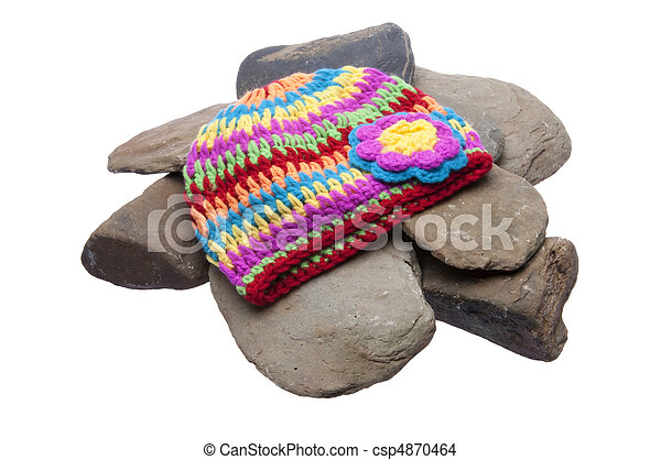 Brightly colored hat sits on a pile of smooth rover rocks. Isolated on a white background with a clipping path. - csp4870464