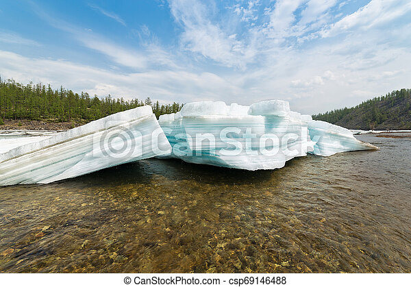 Broken blocks of turquoise layered ice on the river - csp69146488
