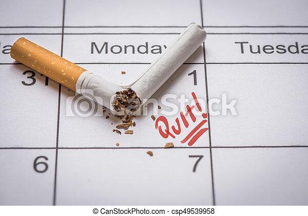 Broken cigarette on calendar. Time to quit smoking concept - csp49539958