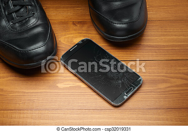 Broken smartphone dropped on shoes