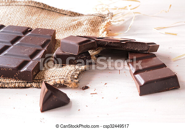 Broken tablet artisan chocolate on a wooden table elevated view - csp32449517
