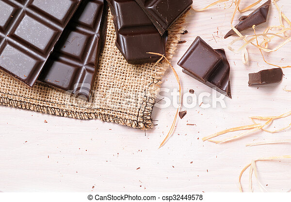 Broken tablet artisan chocolate on a wooden table top view - csp32449578