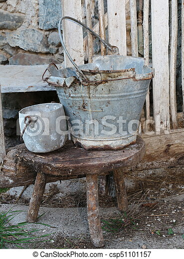 broken tin bucket and an pot over the stool of the old stable - csp51101157