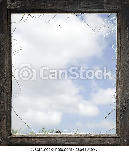 Broken window with old wooden frame, sky background.