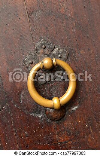 Bronze metal antique vintage door knock or knocker on an old wood door - csp77997003