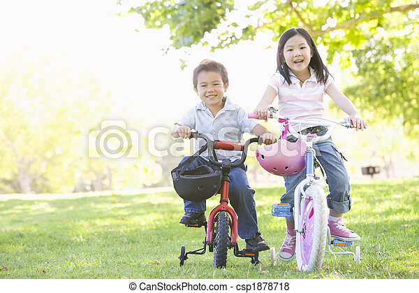 Brother and sister outdoors on bicycles smiling - csp1878718