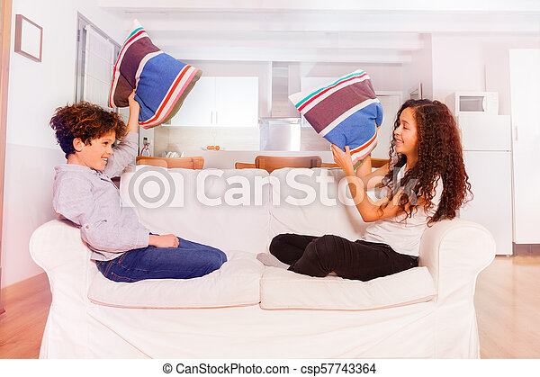 Brother and sister pillow fighting in living room - csp57743364