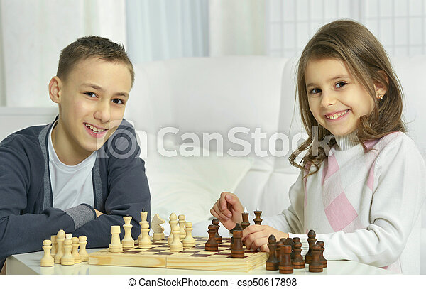 brother and sister playing chess - csp50617898