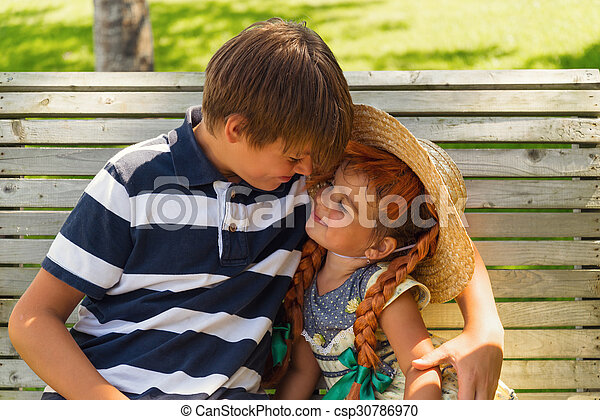 Brother and sister playing together sitting on bench outdoors - csp30786970