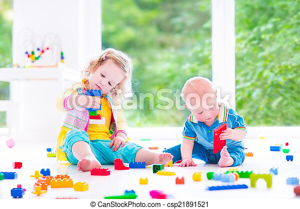Brother and sister playing with colorful blocks - csp21891521