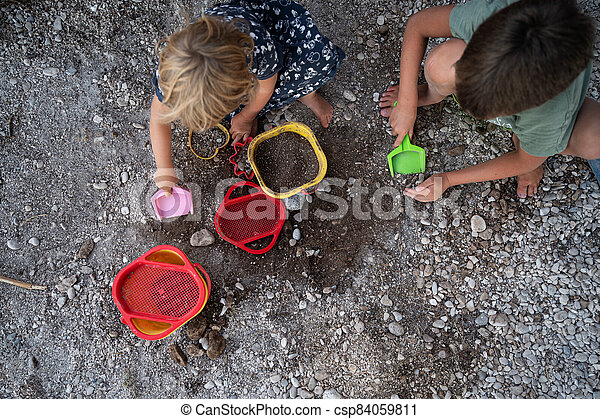 Brother and sister playing with pebbles, dirt and sand toys - csp84059811
