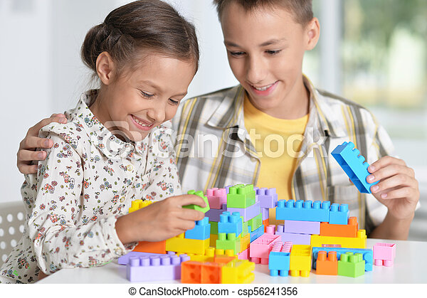 Brother and sister playing with plastic blocks - csp56241356