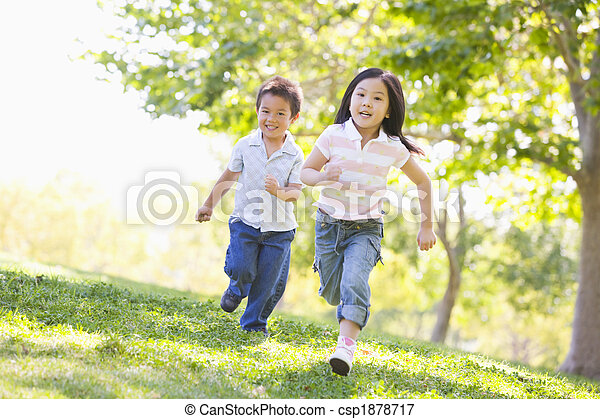 Brother and sister running outdoors smiling - csp1878717