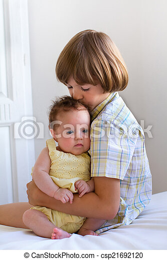 Brother kissing his baby sister - csp21692120