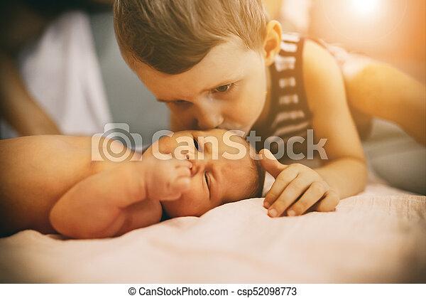 Brother kissing little newborn sister - csp52098773