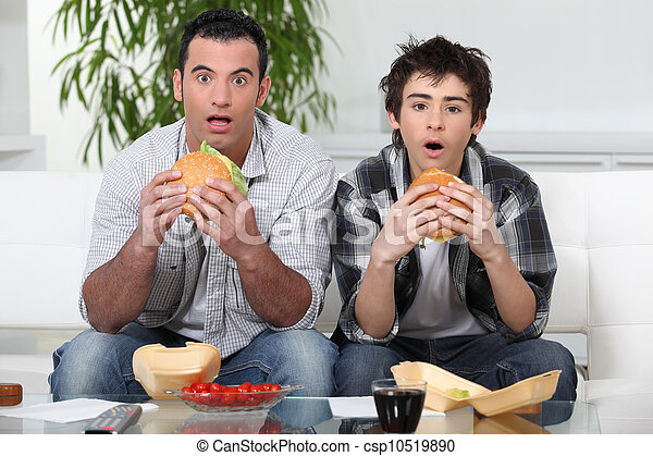 Brothers staring in amazement while eating a hamburger - csp10519890
