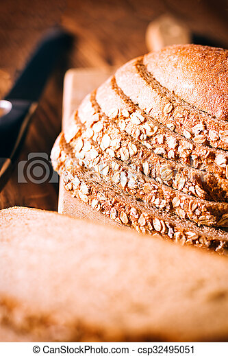 Brown bread on an old wooden table - csp32495051
