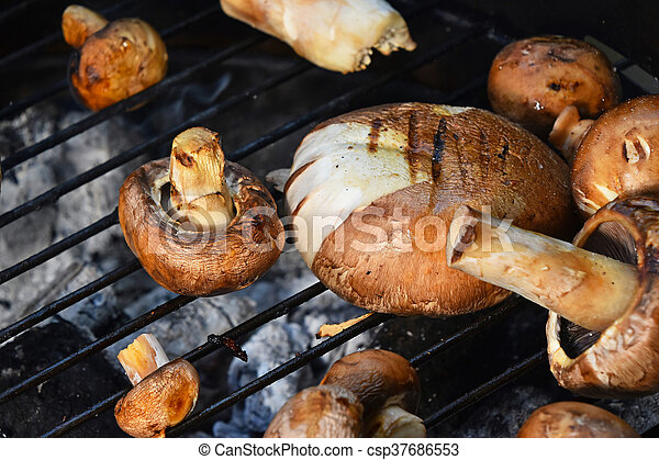 Brown champignons mushrooms on grill - csp37686553