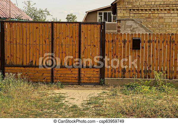 brown closed wooden gate and part of the fence of boards outside in the grass - csp63959749