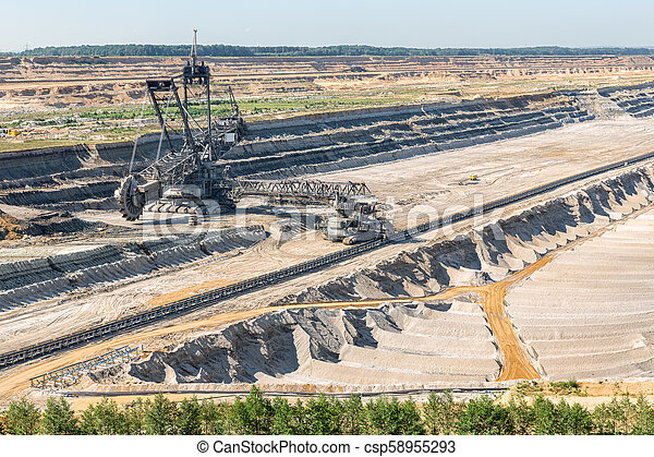Brown Coal Open Pit Landscape With Digging Excavator In Germany Brown Coal Open Pit Landscape With Enormous Digging Excavator In Hambach Mine Germany This Machine Is The Biggest Vehicle In The