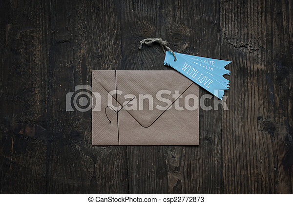 brown envelope on wooden background with love tag - csp22772873