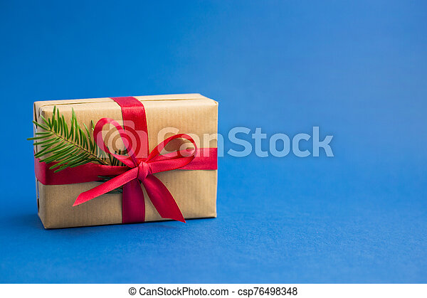 Brown gift boxes with red ribbons and fir tree branch on blue trendy background. Color of the year. Present for Christmas - csp76498348