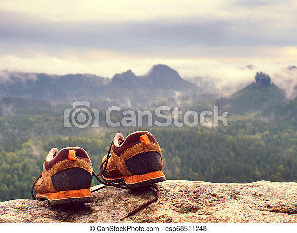 Brown hiking boots on rocks in front of mountain range - csp68511248