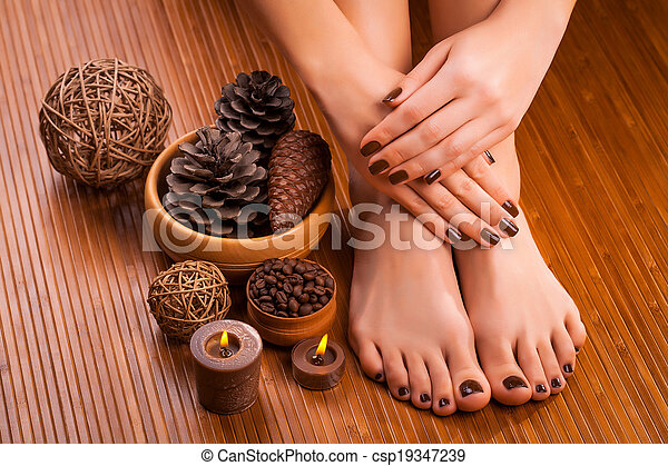 brown manicure and pedicure on the bamboo - csp19347239