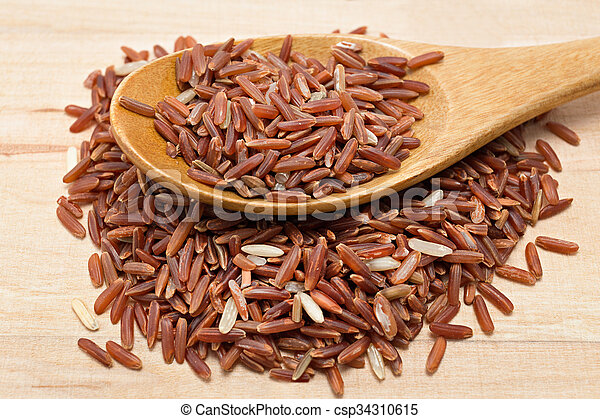 Brown rice on wooden spoon - csp34310615