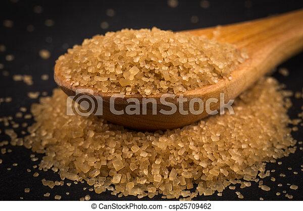 Brown sugar in wooden spoon on dark background - csp25709462