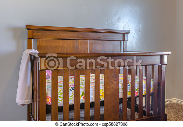 Brown wooden baby crib with blanket - csp58827308