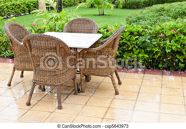 Brown wooden chairs an tables on patio - csp5643973