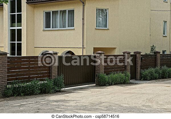 brown wooden fence and gate in the grass near the road near a large house with windows - csp58714516