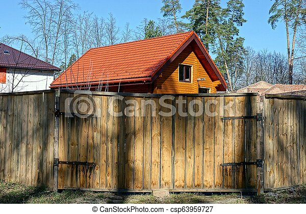 brown wooden gate and a fence of boards outside in the grass - csp63959727