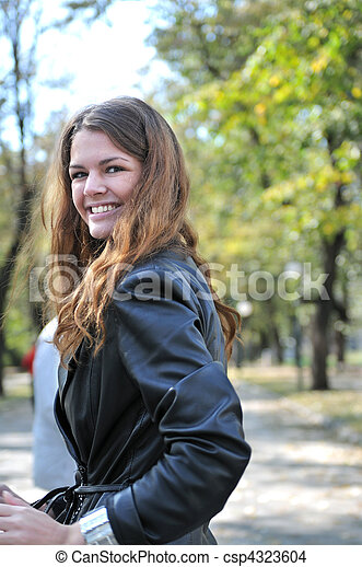brunette Cute young woman smiling outdoors in nature - csp4323604