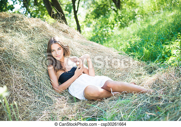Brunette girl is lying on haystack in summer sunny day - csp30261664