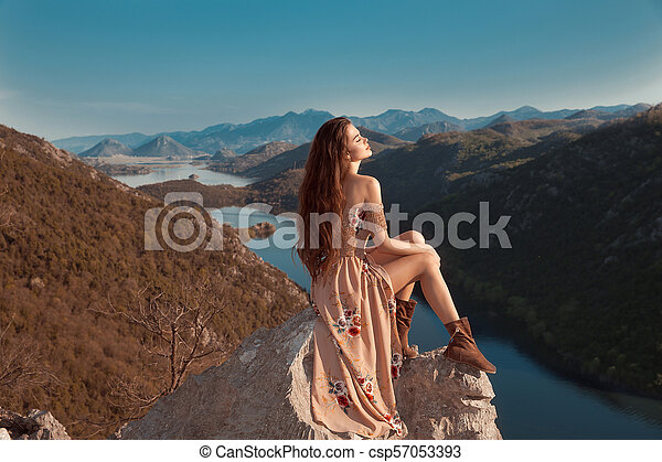 Brunette girl tourist in beige dress sightseeing of Rijeka Crnojevica, Montenegro. Skadar lake national park, Pavlova Strana. Viewpoint Ridge mountains panoramaic landscape. - csp57053393