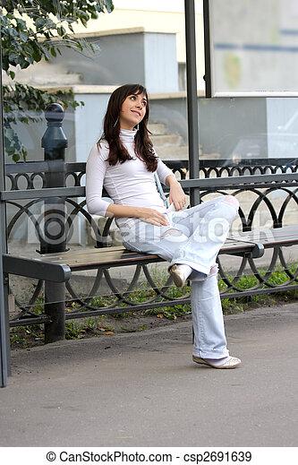 Brunette listening music at bus-stop - csp2691639