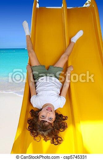 Brunette little girl upside down playground slide - csp5745331