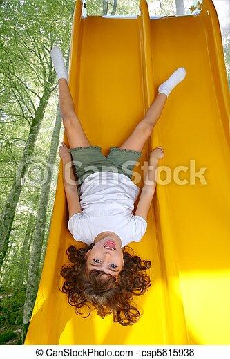 Brunette little girl upside down playground slide - csp5815938