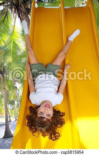 Brunette little girl upside down playground slide - csp5815954