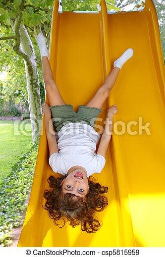Brunette little girl upside down playground slide - csp5815959