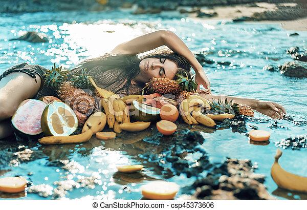 Brunette model posing with lots of healthy tropical fruit - csp45373606