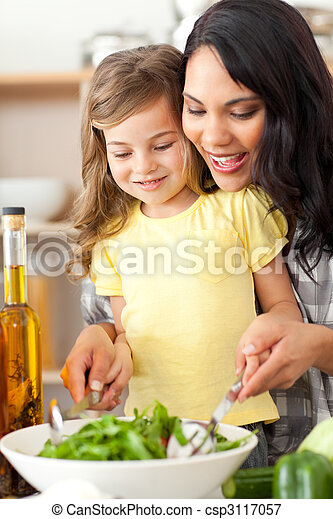 Brunette mother helping her daughter prepare salad - csp3117057
