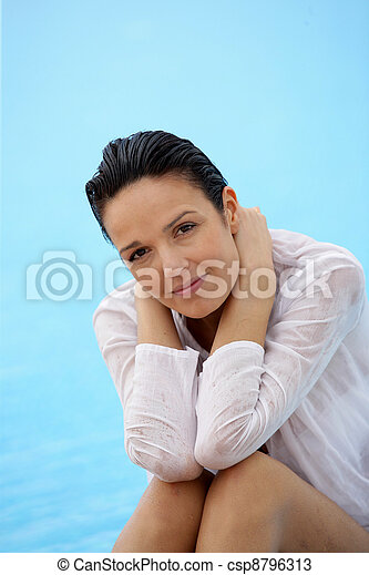 Brunette sat by pool in wet shirt - csp8796313