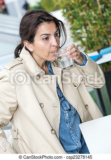 Brunette woman drinking a glass of water - csp23278145