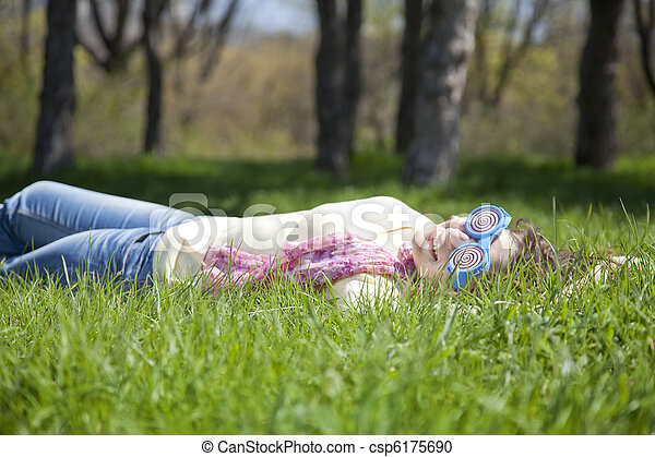 Brunette woman in funny glasses lies at meadow. - csp6175690